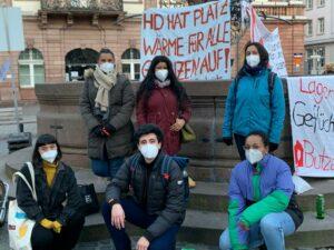 Das Antirassismus Referat blickt in die Kamera. Sie tragen Masken und stehen vor Bannern, um zu protestieren.