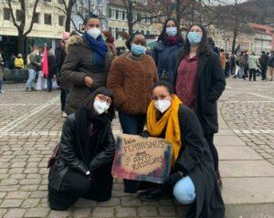 Die Teilnehmer:innen der Demonstration am 8. März stehen mit einem Schild auf dem Marktplatz der Universität Heidelberg und schauen in die Kamera.